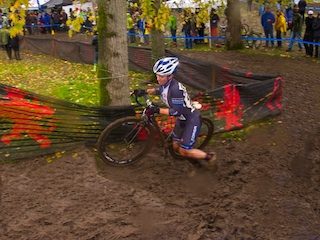 Megan Chinburg pushing bicycle up a muddy track in a bicycle race.