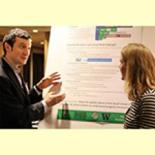 Professor Hornoff presenting poster to another person